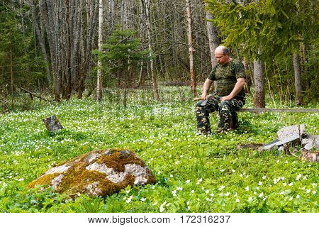 Springtime Is The Moment For Flower. Snowdrop Anemone. Man With An Ax  Sitting On A Bench In The For