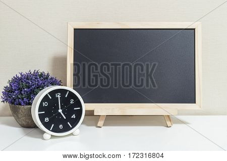 Closeup alarm clock for decorate show 5 o'clock with wood black board on white wood desk and cream wallpaper textured background selective focus at the clock