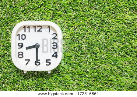 Closeup white clock for decorate show a half past seven or 8:30 a.m. on green artificial grass floor textured background with copy space