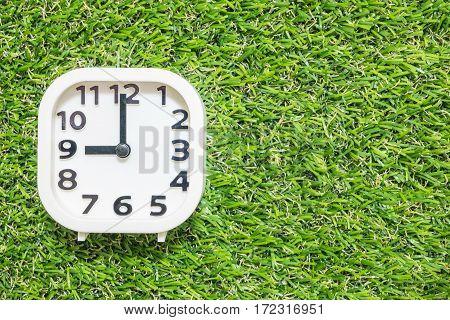 Closeup white clock for decorate in 9 o'clock on green artificial grass floor textured background with copy space