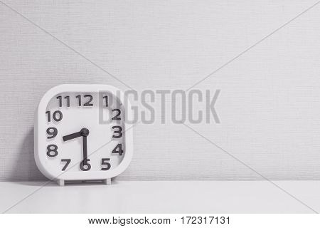 Closeup white clock for decorate show half past eight or 8:30 a.m. on white wood desk and cream wallpaper textured background in black and white tone with copy space