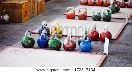 Different sizes of kettlebells weights lying on gym floor.