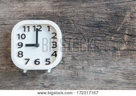 Closeup white clock for decorate in 9 o'clock on old wood floor textured background with copy space