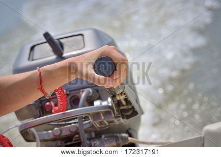 Fisherman hand and boat engine on river