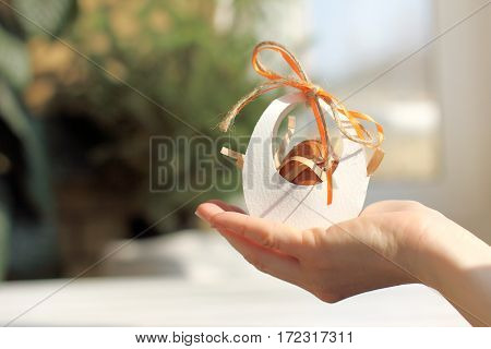 Easter egg in a paper house decorated with an orange ribbon in his hand against the window / yearly holiday preparation