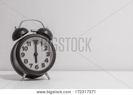 Closeup alarm clock for decorate in 6 o'clock on white wood desk and cream wallpaper textured background in black and white tone with copy space