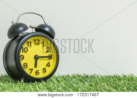 Closeup black and yellow alarm clock for decorate show a quarter past six or 6:15 a.m. on green artificial grass floor and cream wallpaper textured background with copy space