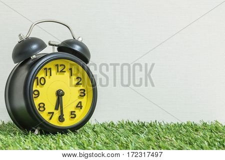 Closeup black and yellow alarm clock for decorate show half past six or 6:30 a.m. on green artificial grass floor and cream wallpaper textured background with copy space
