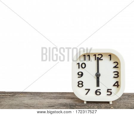 Closeup white clock for decorate in 6 o'clock on old brown wood desk isolated on white background with copy space
