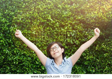 Asian business woman enjoying with her work on grass background. Outstretched arms fresh morning air with sunlight. Nature office. Happiness glasses girl relaxing. Breathing fresh air. copy space.