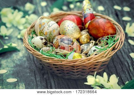 Easter - basket with Easter eggs, Easter decorations on rustic table