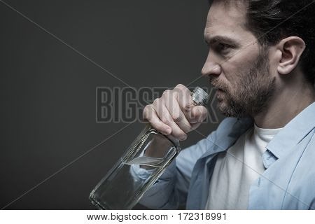 Soothing pain. Thoughtful male person looking ahead with confidence holding glass bottle posing in profile, isolated on grey