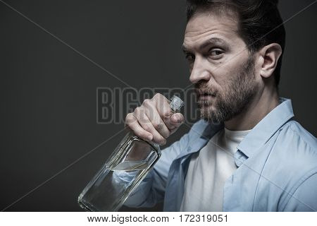 Do not look. Portrait of serious bearded man holding glass bottle in right hand while posing in profile, isolated on grey