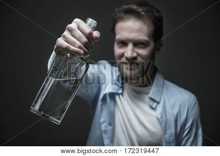 Good mood. Portrait of addicted male keeping glass bottle in right hand while posing in studio, isolated on grey