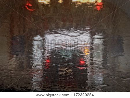 Raindrops on a window glass of a dwelling, where part of the car is seen in the background. Water and rain drops on the glass, abstract view, Drops of rain on glass. Bad weather. Raining season