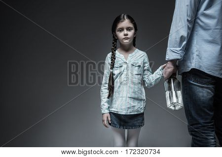 Suffer from it. Melancholy young female person wearing jeans skirt and striped shirt keeping her braid on the shoulder standing while looking straight at camera