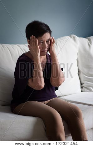 Illness Ill exhausted tired disease concepts. Senior Asian woman sitting on white sofa and having headache.