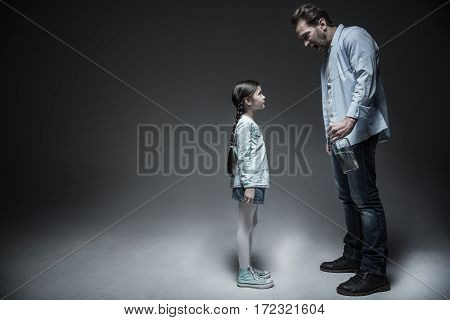 Scene of confusion. Little pretty brunette girl having two long braids wearing jeans skirt and striped shirt posing in semi position, isolated on grey