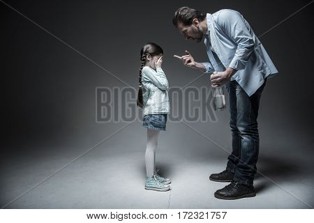Do not irritate me. Poor little girl hiding her eyes from her dad wearing jeans skirt and striped shirt standing in semi position over grey background