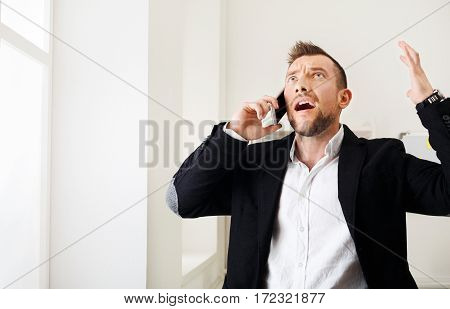 Young stressed businessman shout making call with mobile phone near window in modern office. Annoyed, frustrated man has unpleasant conversation, show negative emotion. Place for copy space