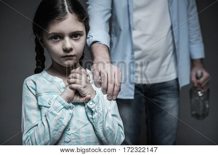 Help me. Frightened little lady keeping her eyes widely opened looking straight at camera while standing in front of her father