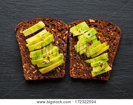 Sliced avocado on dark rye grain bread toast with spices. Sandwich for breakfast and lunch. Snacks. Healthy and vegetarian food. Black slate stone background. Top view.