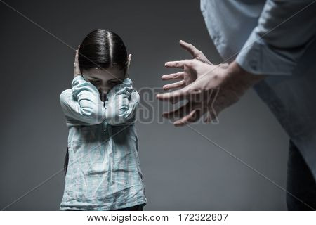 Do not hear you. Sad little girl wearing casual clothes being afraid of the violence of her father keeping her eyes closed