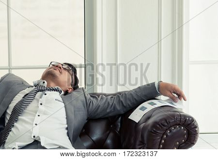 Businessman exhausted and tired from overtime working He sleep on leather sofa