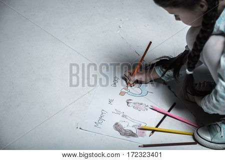 Look at this. Lonely girl from unhappy family holding colorful pencil in right hand while drawing her father sitting on the floor