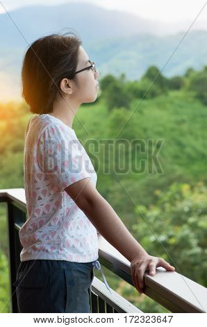 Asian woman standing at balcony and breathing fresh air on the natural landscape background.