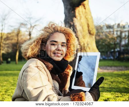 young cute blond african american girl student holding tablet and smiling, lifestyle people concept close up