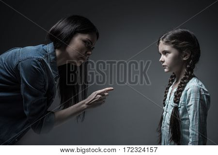 You should listen to me. Little scared girl with two braids wearing light blue shirt standing in semi position while looking at her mother
