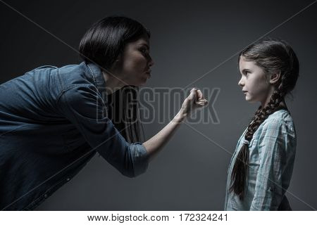 Listen to me. Little girl with two braids wearing light blue shirt standing in semi position while looking at fist of her mother