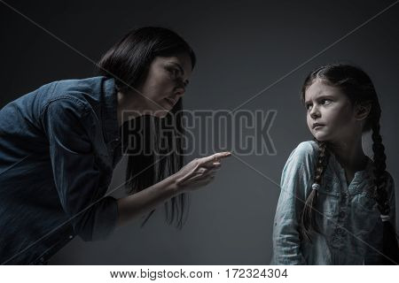 Turn to me. Angry brunette woman wearing jeans shirt threaten her daughter with punishment while standing in semi position