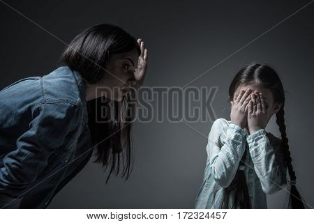 Look at me. Little girl with two braids wearing light blue shirt hiding her eyes from mother standing over grey background