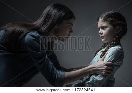Get what one deserves. Scared girl with two braids wearing light blue shirt standing in semi position while looking at fist of her mother