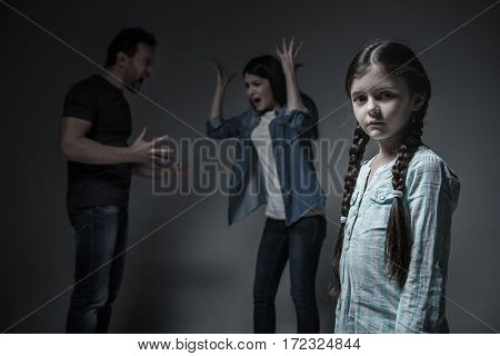 Do not quarrel. Young family couple using gesticulation while sorting out their relationship standing behind their daughter
