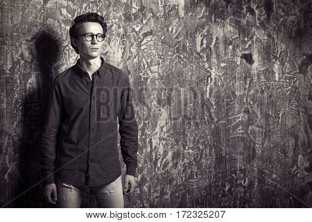 Portrait of young man in casual jeans clothes and spectacles posing over grunge background. Men's beauty, fashion. Optics style.