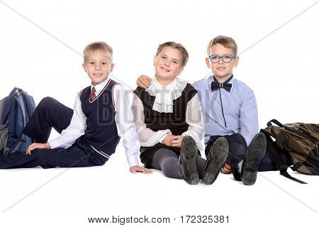 Portrait of three happy school friends posing together at studio. School uniform. Education. Isolated over white.