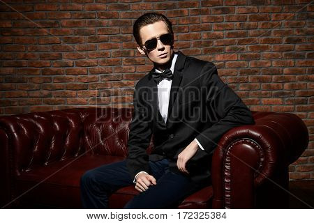 Portrait of an imposing well dressed man in sunglasses. Luxury. Men's beauty, fashion.