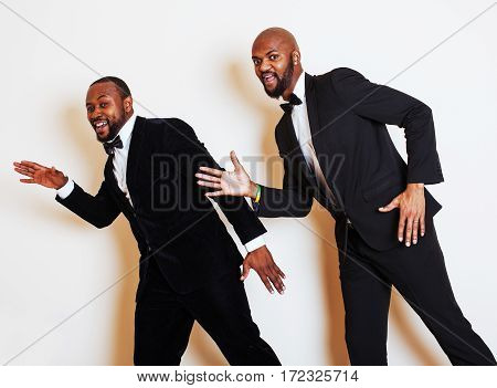 two afro-american businessmen in black suits emotional posing, gesturing, smiling. wearing bow-ties entertaiment stuff close up