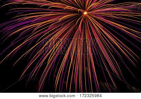 A red firework shot off in the night sky