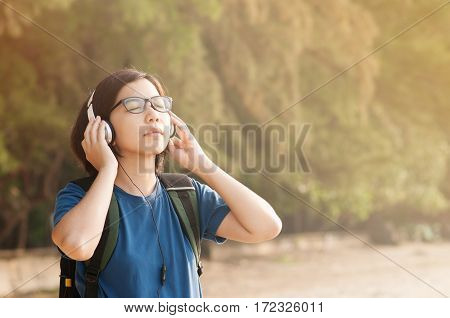 Happiness of Young Asian woman listening music with headphone in nature. Beautiful glasses girl closed her eyes and breathing fresh air.