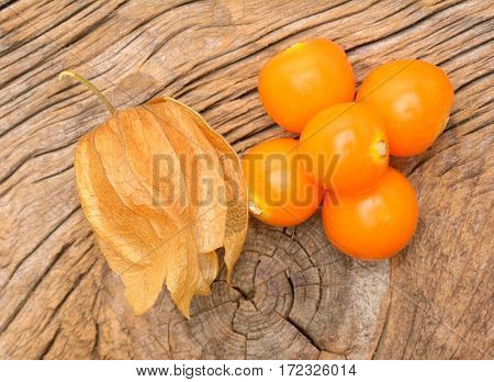 ripe physalis on wooden background in studio