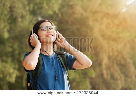 Happiness of Young Asian woman listening music with headphone in nature. Beautiful glasses girl closed her eyes and smiling with fresh air.