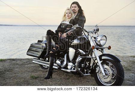 Young beautiful couple posing on a bike