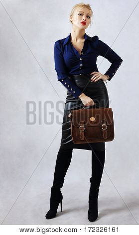 Portrait of beautiful young businesswoman in blue shirt with purse poster