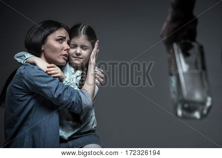 Stop drink. Frightened girl keeping her eyes closed putting her hands around neck of her mother while sitting on the knees