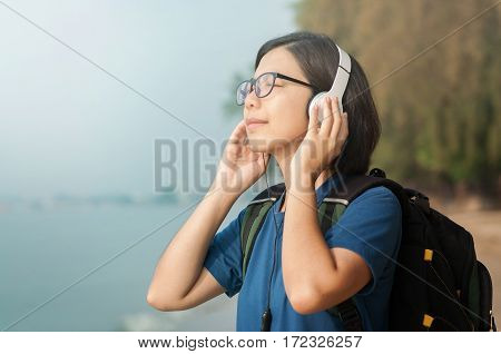 Happiness of Young Asian woman listening music with headphone on sae background. copy space. Beautiful glasses girl closed her eyes and smiling with fresh air.