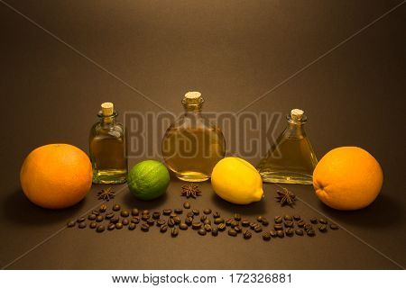 Three vintage glass bottles with lime, grapefruit, lemon orange and coffee beans and anis stars on brown background